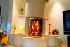 Ein eleganter und moderner Kachelofen mit großer vergoldeter Panorama-Sichtscheibe nach traditioneller Bauart.